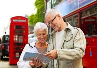 family, age, tourism, travel and people concept - senior couple with map over london city street background